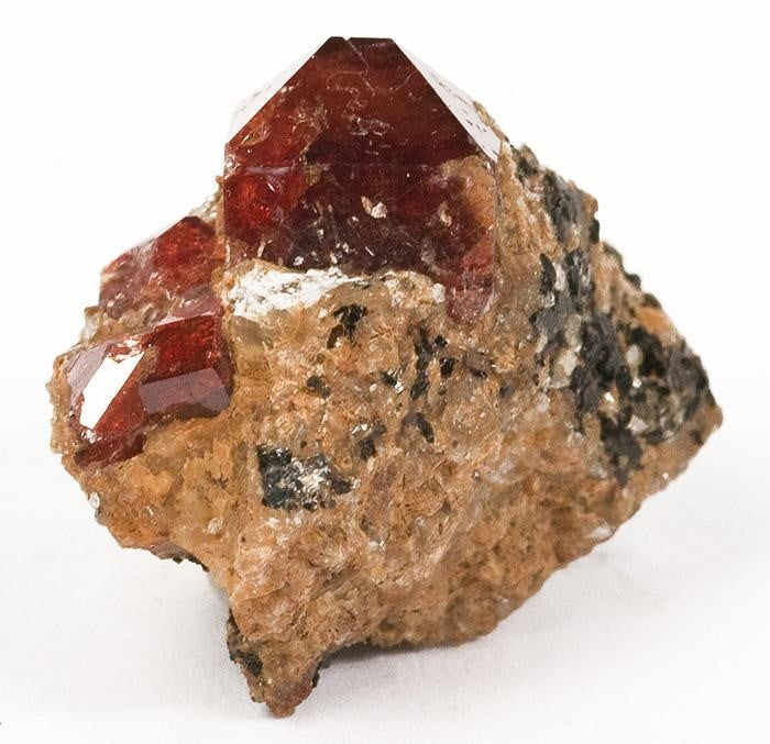 Aesthetically perched high on a matrix of quartz and biotite mica, are a few, equant, glassy and gemmy, orange-red, zircon crystals, to 9mm