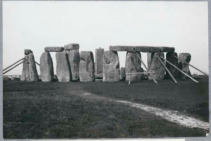 General view looking south west showing stones of the outer circle propped with timbers. Photo taken in 1919. The tallest upright, Stone 56 of the fallen T3, the central trilithon, straightened in 1901.